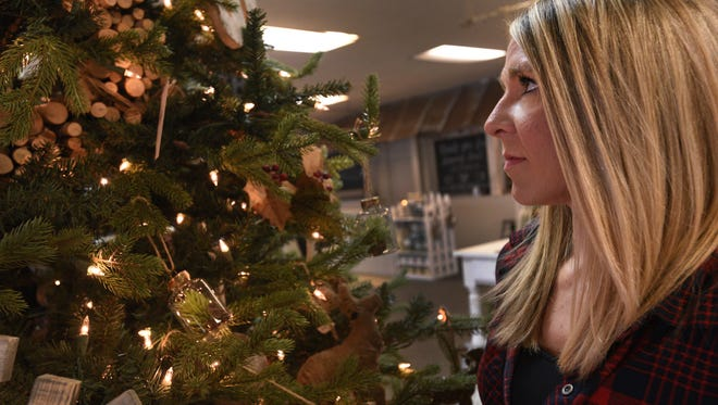Dana Smyth checks the arrangement of  holiday decorations at Bossier City's Ivy and Stone.