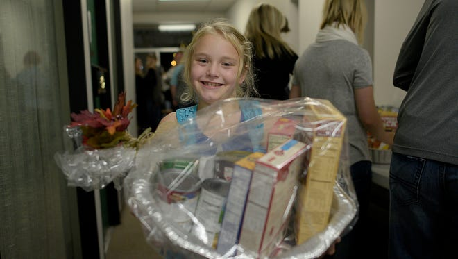 Sossity Mores, 9, poses for a photo with a Thanksgiving basket she made.   JUNFU HAN | STAFF PHOTOGRAPHER