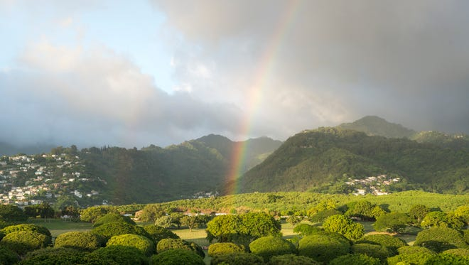 A rainbow appears over the center of the Punchbowl Crater, National Memorial Cemetery of the Pacific.
