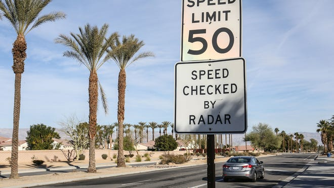 A car passes by a speed limit sign on Miles Avenue in La Quinta. Miles is one of several streets where the speed limit is dropping.