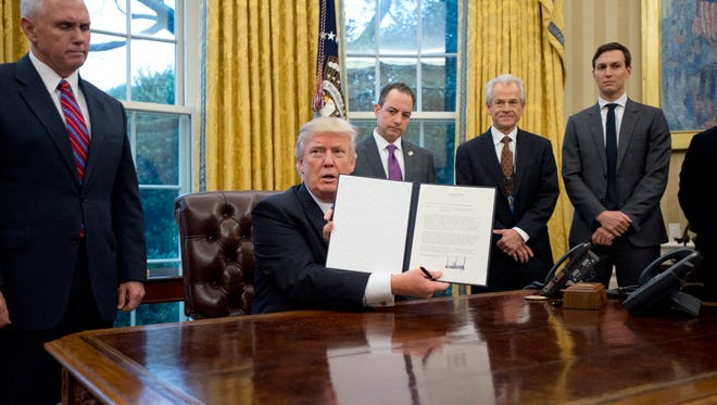 President Donald Trump shows the executive order withdrawing the U.S. from the Trans-Pacific Partnership (TPP) after signing it in the Oval Office on Jan. 23, 2017.