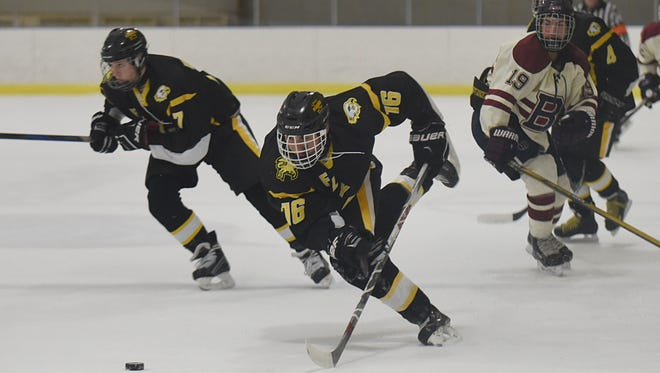 Farmington Hills sophomore forward  Ben McColl (middle) dives for a loose puck during Wednesday's victory over Berkley.