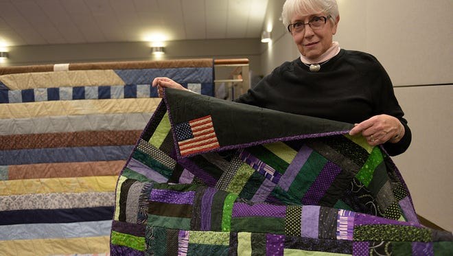 Susan Horner shows the quilt she made to donate to Piquette Square.