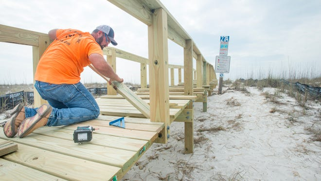 J. Miller Construction employees work on several new walkovers are being constructed to protect the dunes and vegetation along Pensacola Beach on Tuesday, March 7, 2017.