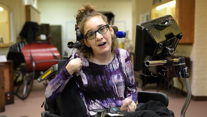 Sarah Palk has a developmental disability, uses a wheelchair and communicates on a laptop with the touch of a button she controls with her head.