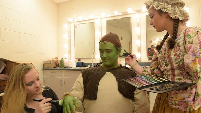 Made Foster (left) and Victoria Factor help to put make up on Daniel Isabella (Shrek).
