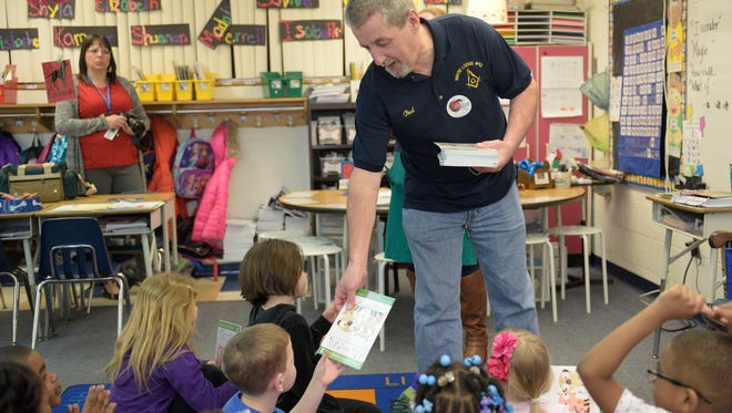 Wayne Lodge member Bud Prough gives a book to a first-grader at Edison Elementary School.