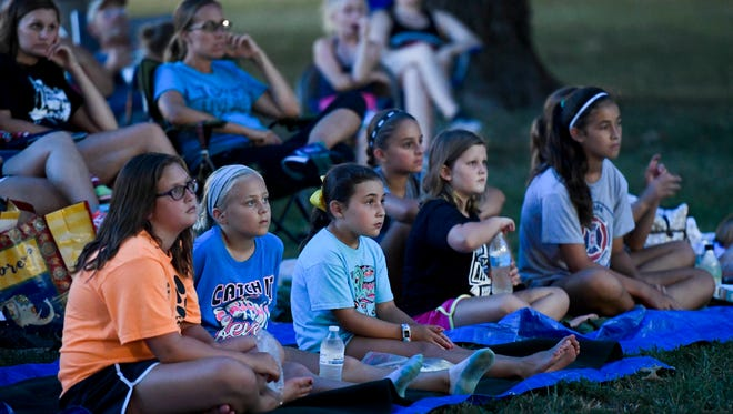 """Sitting on blankets on the West Branch Library lawn, movie fans watch """"Honey I Shrunk the Kids"""" at the Movies in the Park sponsored by the Franklin Street Events Association Sunday, July 23, 2017."""