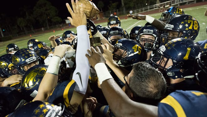 Naples players celebrate winning the Joe Klimas Trophy, known as 'the nut,' after beating Lely 42-7 to win the Coconut Bowl at Naples High Friday night, October 6, 2017.