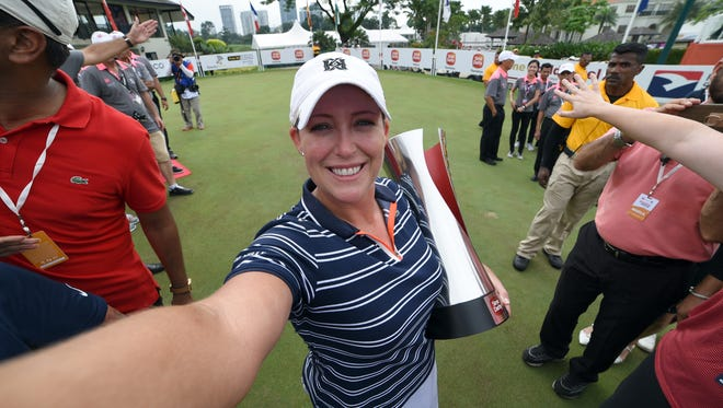 Cristie Kerr of the United States imitates a selfie as she poses with the trophy for the Sime Darby LPGA Malaysia.