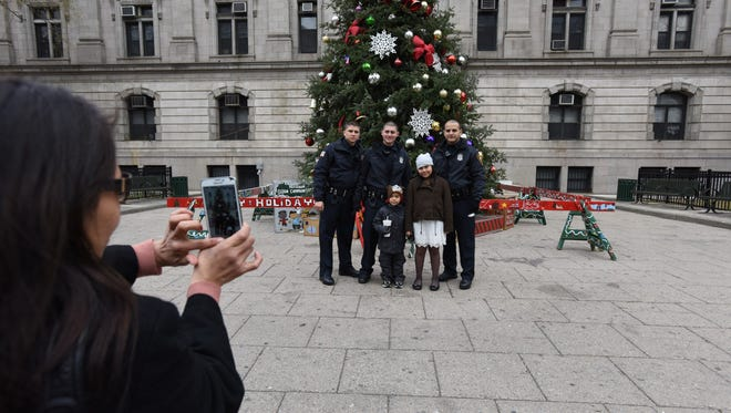 Paterson Police Officers Thomas Giaquinto, Sebastian Gomez and Luis Fernandez have their photo taken with kids who were passing by the Paterson Christmas tree in December 2014.