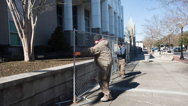 Chris Dismukes, left, and Jon Stetz with the Hagen Fence Co. erect a temporary fence on Wednesday, Jan. 17, 2018, around the U.S. DistrictCourthouse at 1 N. Palafox St. in downtown Pensacola.