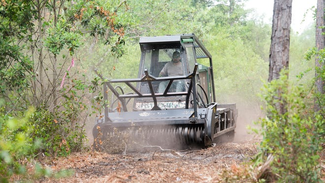 """Firefighter Chase Crow demonstrates how his Gyro-Trac mulching machine, nicknamed """"Barbara Jean"""", is used to create a fire break as part of the Florida Forest Service's wildfire mitigation in Navarre on Tuesday, May 15, 2018."""