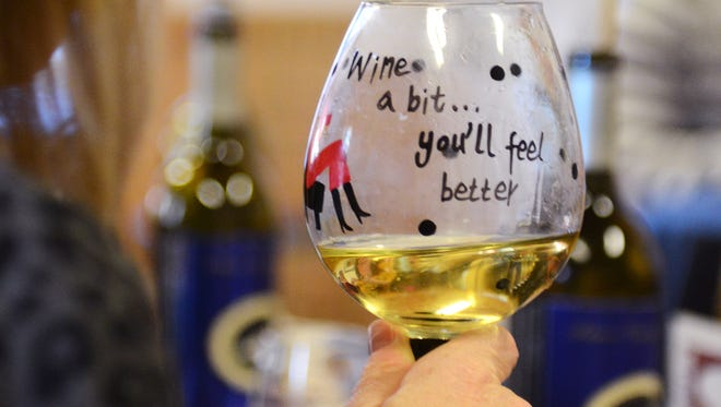 "A woman raises a glass of wine that says ""Wine a bit...you'll feel better!"" at an event at Adams County Winery in 2013."