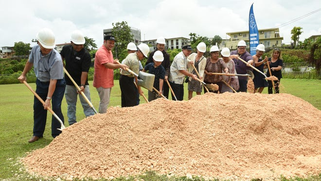 Sinajana Mayor Robert Hofmann, third from left, in joined by Gov. Eddie Calvo, seventh from right, and others at a groundbreaking ceremony for the Sinajana baseball field upgrade project on July 12, 2018.