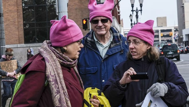 Geraldine Grunow, left, her husband Ken and Betsy Cohn all from Detroit wear matching pink hats at the Women's March on Lansing Saturday, January 21, 2017. Between 8,000 and 9,000 protesters attended the event.