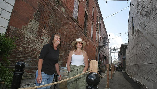 Holly Graber (left), owner of the Hideaway Lounge, and Dori Heck, owner of the Sangria Stand, discuss the additional outside seating area that has helped to expand their downtown Massillon businesses amid the coronavirus