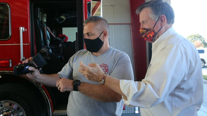 From left, Lee Echols of Bethlehem Volunteer Fire Department shows North Carolina Insurance Commissioner and State Fire Marshal Mike Causey the thermal cameras that were purchased with a grant.