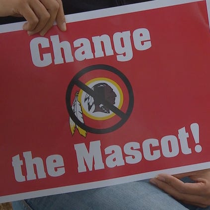 A sign held by a protester of the Redskins' team name.