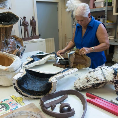 Fairhope Foundry assistant, Sheila Swindle, coats the