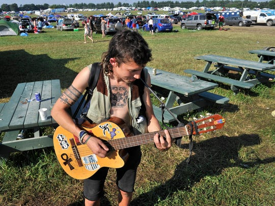 Bobby Zimmerman of Chattanooga plays guitar on the campgrounds as he waits for his friend to pack on the last day of the Bonnaroo Music & Arts Festival on June 16, 2014, in Manchester, Tenn.