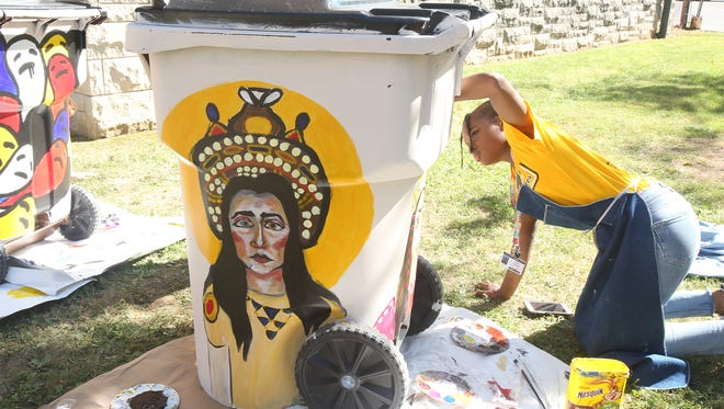 duPont Manual High School students Paint trash bins to collect clothes for charity