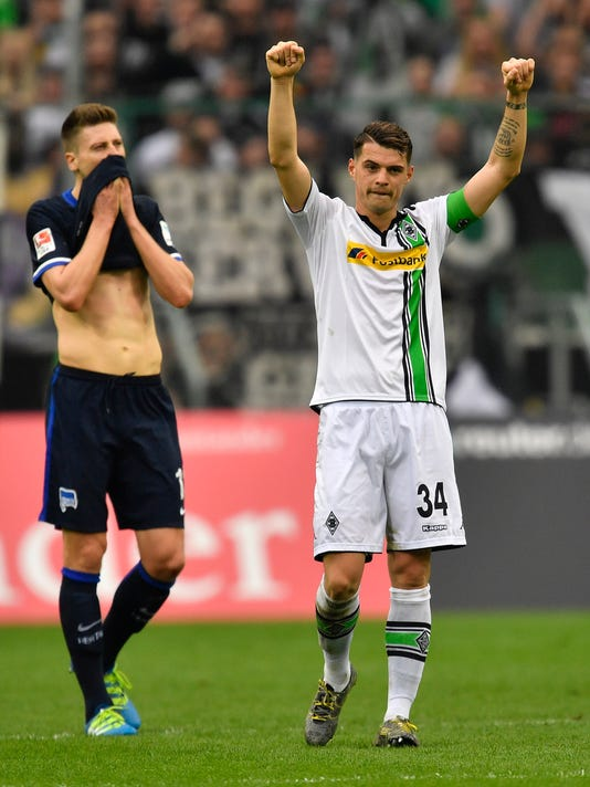 Moenchengladbach's Granit Xhaka, right, celebrates beside Berlin's disappointed Jens Hegeler after the German Bundesliga soccer match between Borussia Moenchengladbach and Hertha BSC Berlin in Moenchengladbach, Germany, Sunday, April 3, 2016. Borussia defeated Berlin with 5-0. (AP Photo/Martin Meissner)