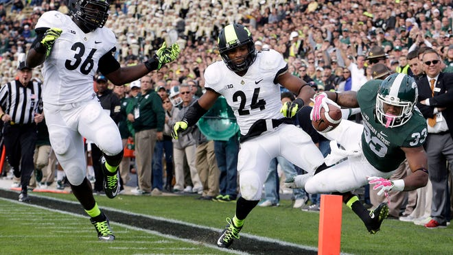 Michigan State running back Jeremy Langford (33) gets forced out of bounds at the one yard line by Purdue defensive back Frankie Williams (24) during the second quarter of an NCAA college football game in West Lafayette, Ind., Saturday, Oct. 11, 2014. Purdue linebacker Danny Ezechukwu (36) trailed the play. (AP Photo/AJ Mast)