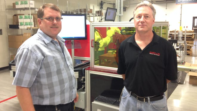 At Wells Manufacturing, Tom Schaefer (left), director of engineering, and Steven Sauvey (right), automation engineering manager, stand in front of a machine used to produce car parts Friday, June 19.