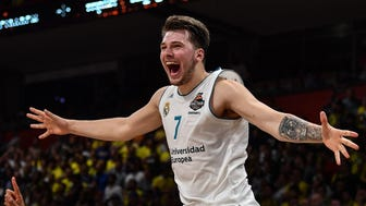 Real Madrid's Slovenian Luka Doncic (C-7) jumps over the barrier as the team celebrates their 85-80 win over Fenerbahce in the Euroleague Final Four finals basketball match between Real Madrid and Fenerbahce Dogus Istanbul at The Stark Arena in Belgrade on May 20, 2018. / AFP PHOTO / Andrej ISAKOVICANDREJ ISAKOVIC/AFP/Getty Images ORIG FILE ID: AFP_1576J1