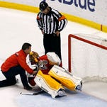 Mar 3, 2015; Sunrise, FL, USA; Florida Panthers trainer David Zenobi attends to injured goalie Roberto Luongo as referee  Justin St. Pierre looks on in the first period at BB&T Center. Mandatory Credit: Robert Mayer-USA TODAY Sports ORG XMIT: USATSI-184982 ORIG FILE ID:  20150303_pjc_bm1_028.JPG