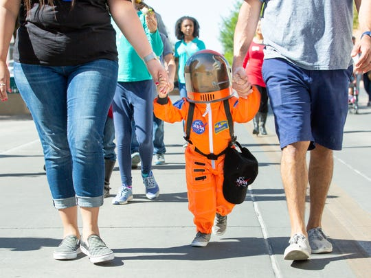 Canelo Gonzalez, 2, of Las Cruces, walks with his parents on Saturday, April 14, 2018 during Las Cruces Space Fest's Space Walk down Main Street.