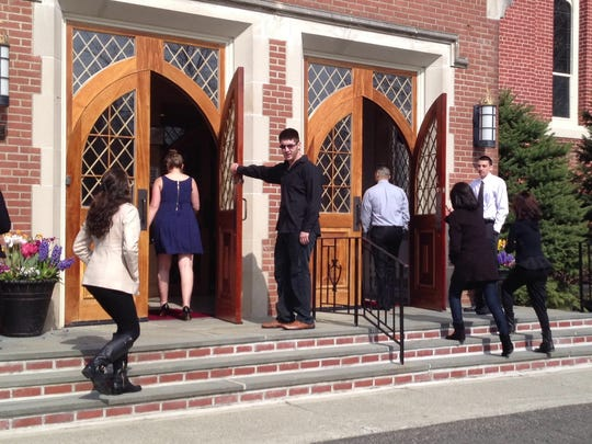 Friends enter St. Mary's Roman Catholic Church in Wappingers Falls for the funeral of Adam Justiniano, who died in a fatal fire on Wednesday.