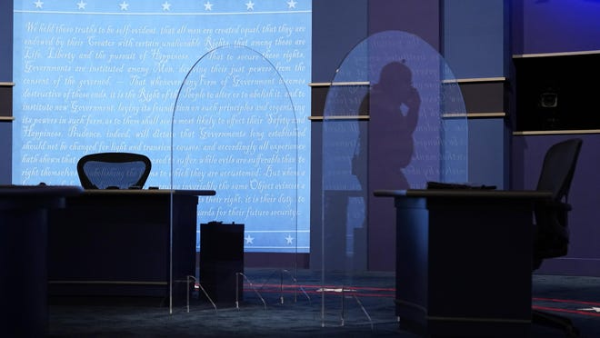 A worker is reflected in a protective plastic panel onstage between tables for Vice President Mike Pence and Democratic vice presidential candidate, Sen. Kamala Harris, D-Calif., as preparations take place for the vice presidential debate in Kingsbury Hall at the University of Utah, Tuesday, Oct. 6, 2020, in Salt Lake City.