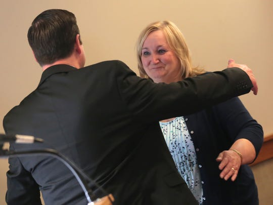 Probation officer Pam Myers hugs Judge Brent Robinson after being presented with a retirement plaque during the 19th annual Richland County Drug Court Graduation on Thursday.