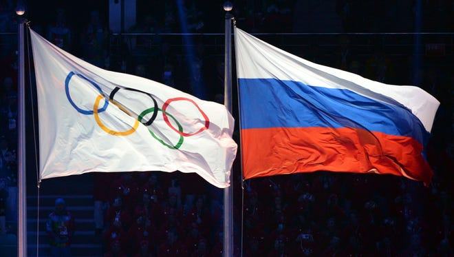 This photo taken on Feb. 7, 2014, in Sochi shows the Olympic and Russian flags being hoisted during the Opening Ceremony of the Sochi Winter Olympics.