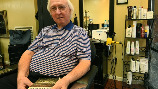 Barber Cecil Groce, at the Urban Salon on Walnut Street, cut Billy Graham's hair when the evangelist came to Knoxville in 1970. Groce remembers the experience from his chair Thursday, Feb. 22, 2018, and holds a signed copy of one of Graham's books he got that day.