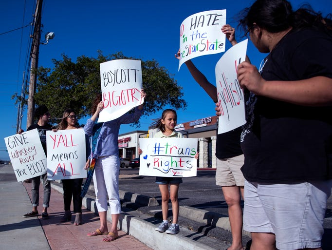 Protesters gather on the sidewalk outside Whiskey River