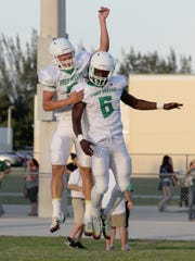 Fort Myers players Dawson DeGroot, left, and Darrian Felix celebrate a touchdown made by Felix against Island Coast Friday in Cape Coral.