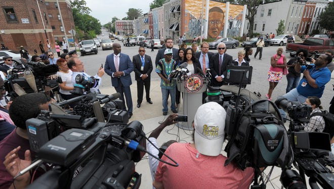 Baltimore State's Attorney Marilyn Mosby, at podium, holds a news conference near the site where Freddie Gray, depicted in mural in background, was arrested after her office dropped the remaining charges against three Baltimore police officers awaiting trial in Gray's death, in Baltimore on July 27, 2016.