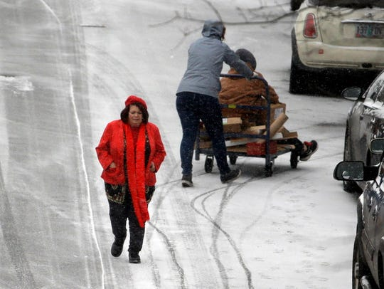 People maneuver on slick roads as a snow storm moves