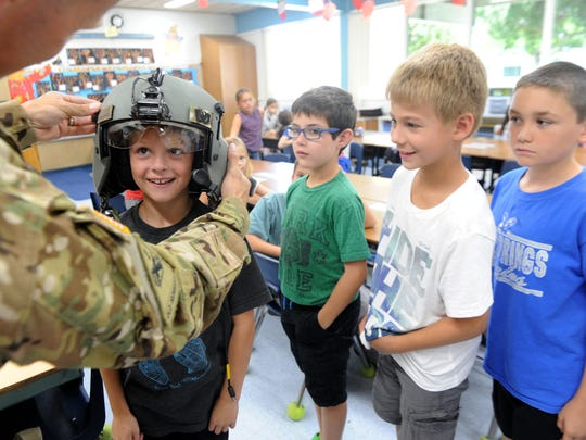 Chief Warrant Officer 2 Kyle Brantner of the California Army National Guard puts his helmet on Kaden Henderson as (from left) Aiden Schneiderman, Connor Pawlik and Jacob McCaskill watch and wait their turn at Big Springs School in Simi Valley. Last year, when the students were in second grade, they corresponded with Brantner while he was in Iraq.