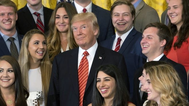 President DonaldTrump poses with an outgoing group of interns at The White House in Washington.