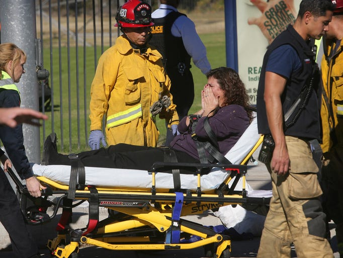 A victim is wheeled away on a stretcher following a