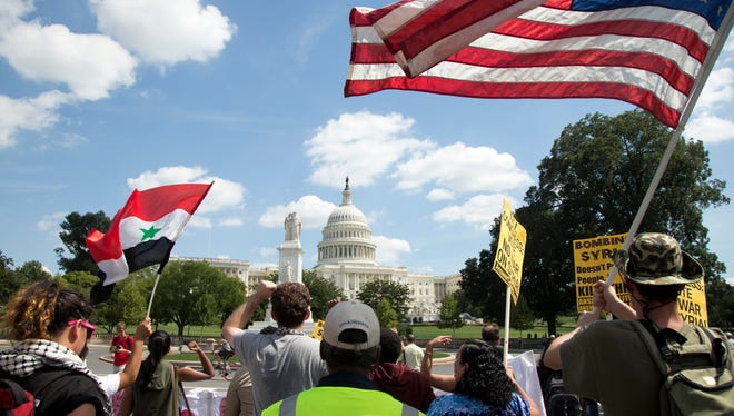 Protesters against U.S. military action in Syria march to Capitol Hill from the White House in Washington on Sept. 7.
