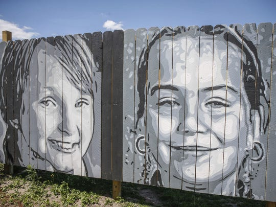 A painting of Elizabeth Collins, left, and Lyric Cook, the two cousins who were abducted July 13, 2012, stands facing freeway traffic from Exchange Park in Evansdale.