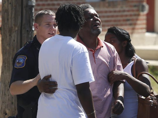 A man is consoled at the scene as Wilmington police investigate in the 600 block of W. 6th Street after a shooting Monday afternoon.