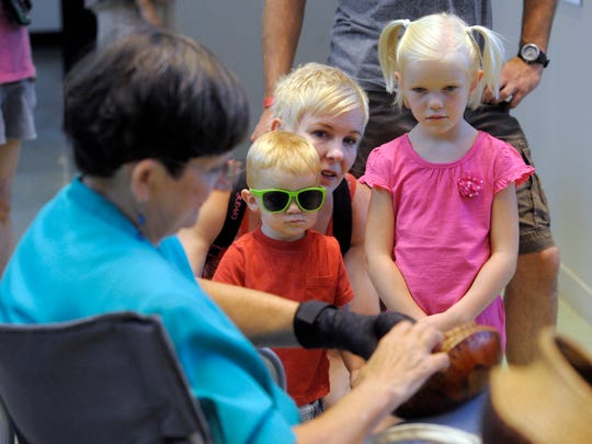 """Brooke LoBue and her kids, Cyrus, 1, and Mia, 5, watch as Toni Best, left, coils pine needles on a gourd during """"History in the Making,"""" a collaboration of the Tulare County Museum and the Arts Consortium Saturday at the Tulare County Museum of Farm Labor and Agriculture located in Mooney Grove Park in Visalia."""