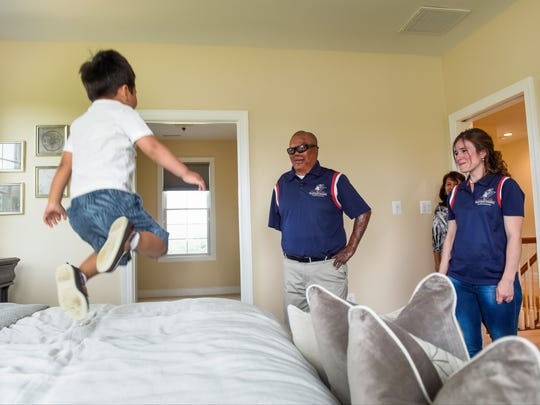 """United States Marine veteran Tony Porta, his wife, Deicy, and his mother, Eva (back), watch Kenneth Charles, 3, bounce on the bed of their new """"smart"""" home."""
