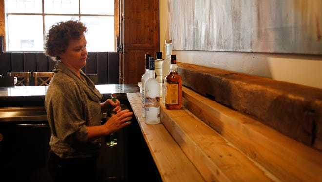 Joan Hutchinson sets up the bar at Rye on Thursday, October 30, 2014, in Appleton, Wis. The liquor shelf in the bar features a beam salvaged from the Jim Beam distillery. The new restaurant will open inside the Copperleaf Hotel on Monday.  Joshua Bessex/ Post-Crescent Media